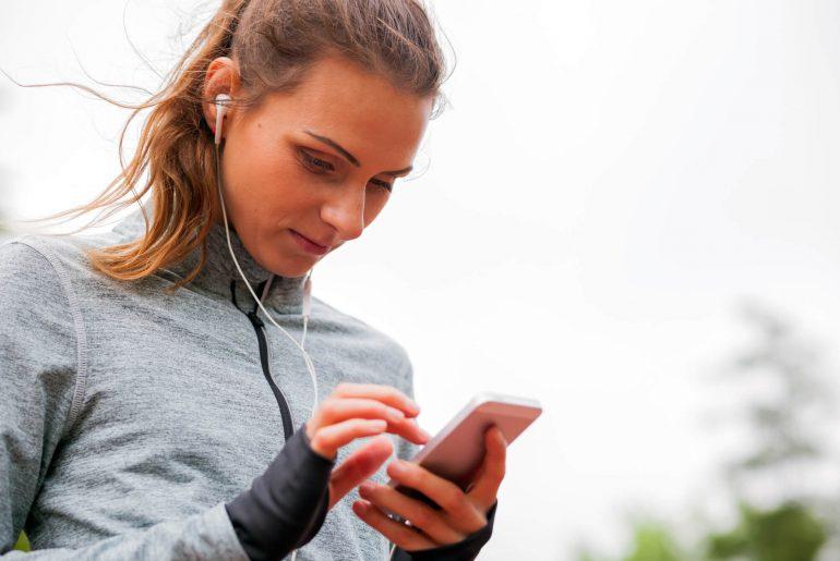 Mulher com fone olhando para celular e vendo aplicativos que podem ajudar a manter sua saúde em dia.