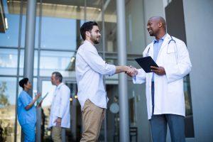 Médico conversando com um rapaz a respeito da saúde do homem com objetivo de convencê-lo a ir em uma consulta.