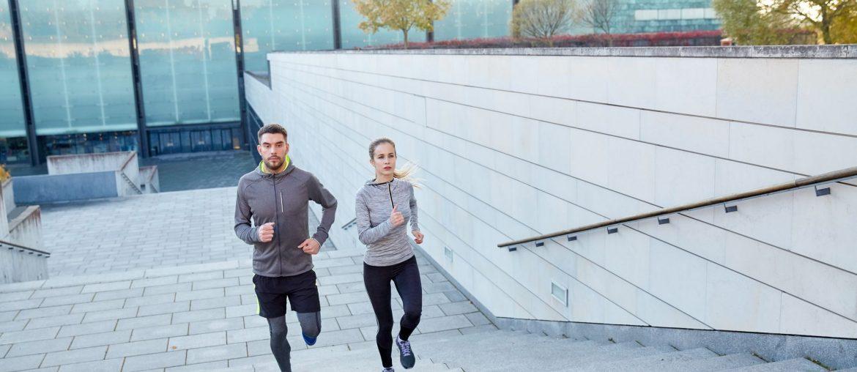 Um casal se exercitando, subindo escadas e seguindo dicas do seu médico para começar a fazer exercícios físicos.
