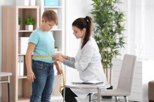 Médica medindo cintura de um jovem paciente para identificar sobrepeso.