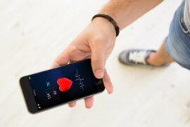 Homem segurando celular com aplicativo de saúde aberto.