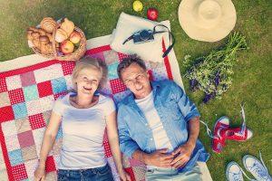 Casal de idosos em pique nique seguindo dicas de como envelhecer com saúde.