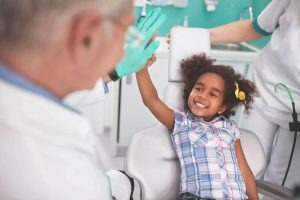 Criança rindo para médico sem medo de ir a uma consulta médica ou dentista.