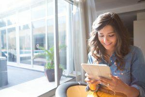 Mulher no quarto realizando um agendamento de consulta online.