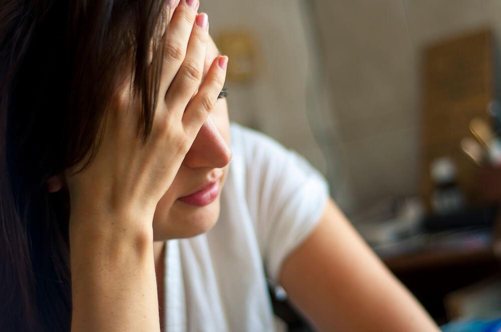 Mulher na sala sendo afetada por dor de cabeça, um dos sintomas do efeito alcoólico.