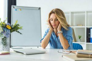 Mulher no trabalho sofrendo sintomas de stress
