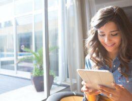 Mulher usando tablet para agendar consulta online.