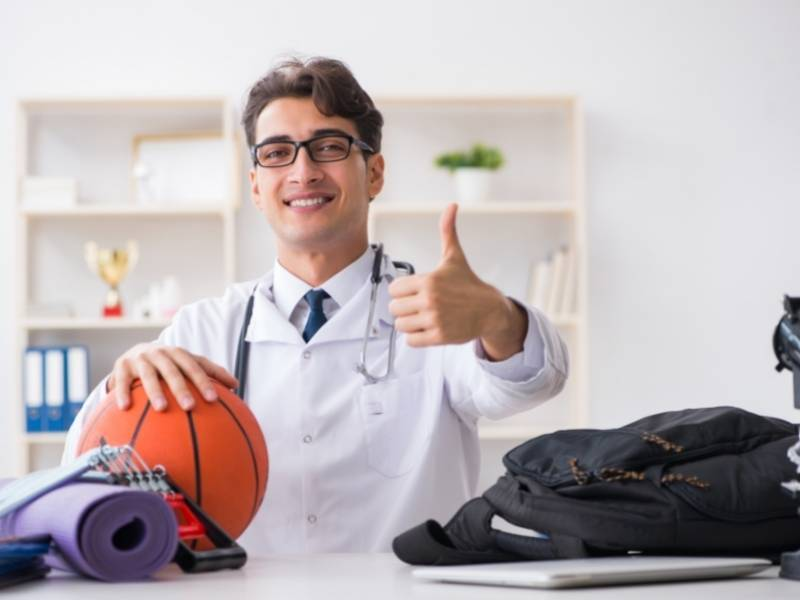 Médico sentado segurando uma bola de basquete fazendo sinal de positivo.