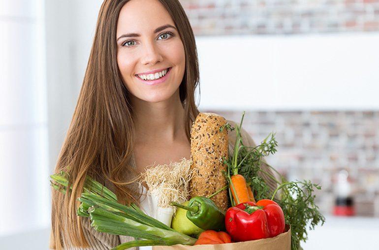 Mulher com cesta de alimentos e feliz por consegui-los digerir adequadamente devido ao uso dos probióticos.