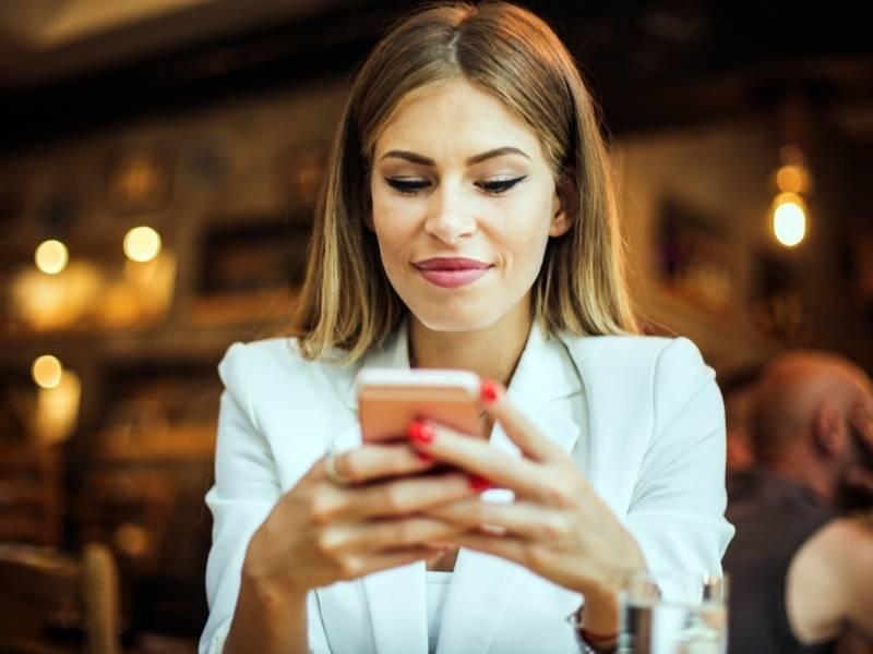 Mulher jovem usando o celular.