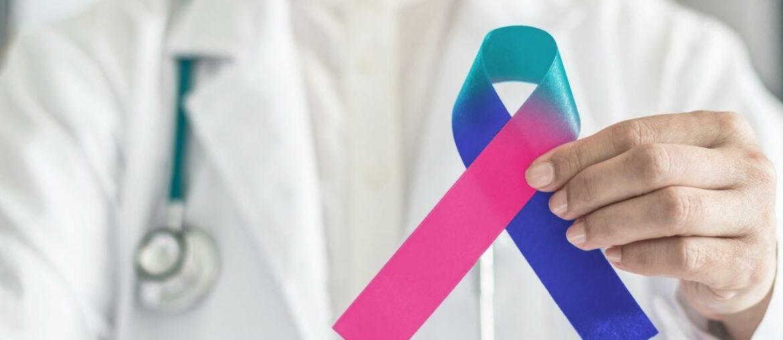 Médico segurando laço símbolo do combate ao câncer.