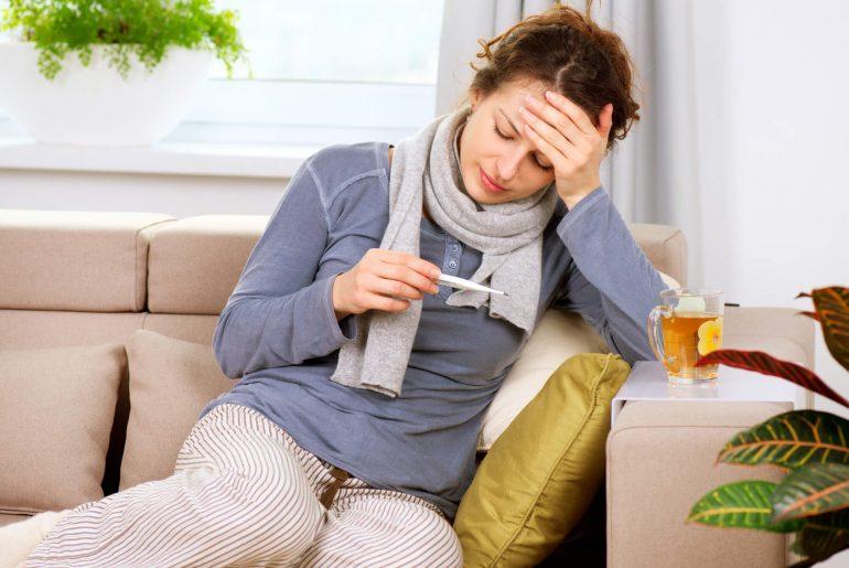 Mulher na sala encostada no sofá sentindo alguns sinais de que é a hora de procurar um médico.