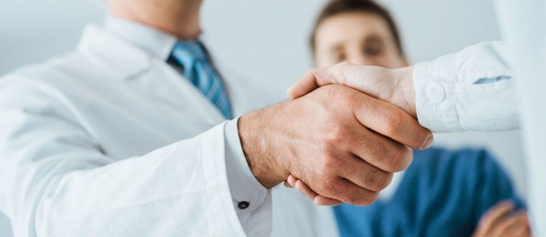 Médicos se cumprimentando e paciente observando. Uma das vantagens de escolher a melhor clínica médica.