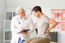 Médico urologista realizando atendimento com paciente homem.