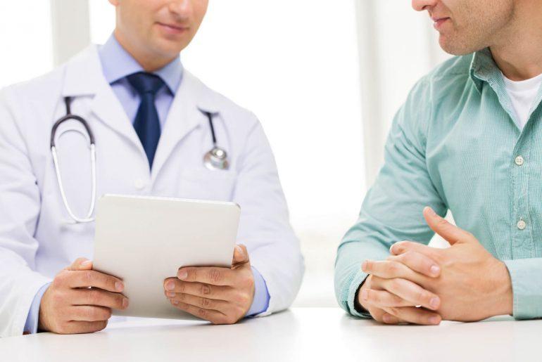 Médico conversando com homem sobre exames periódicos a serem realizados.