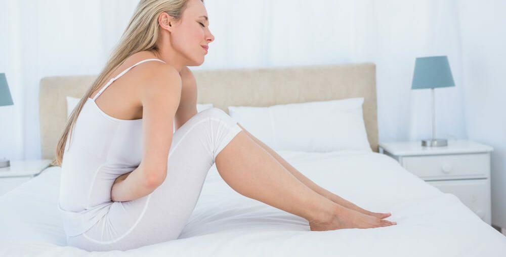 Mulher no quarto de branco sofrenco com sintomas da doença Celíaca