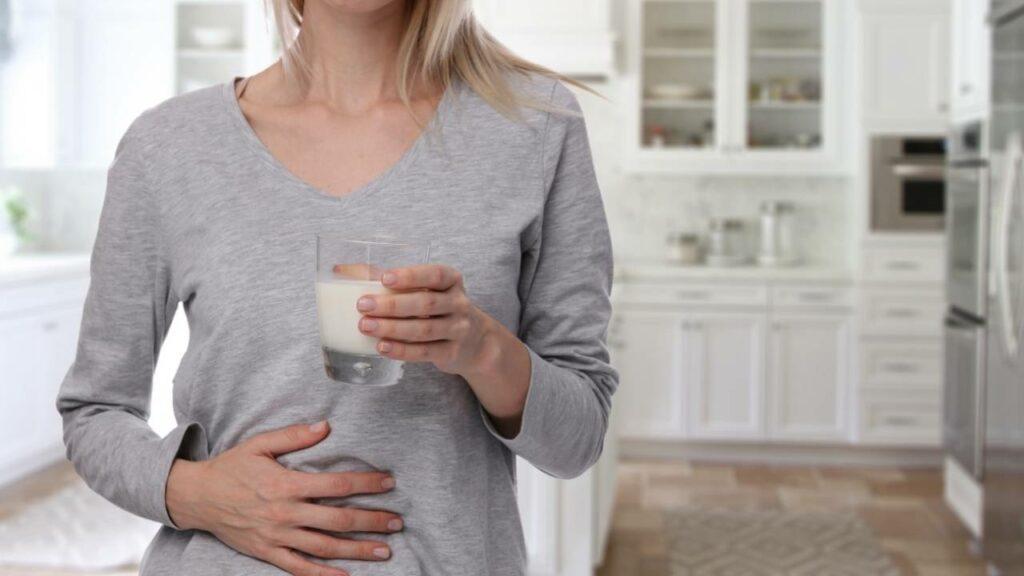Mulher segurando um copo de leite e com a outra mão na barriga.