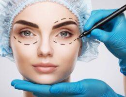 Médico cirurgião plástico realizando contornos no rosto de paciente com uma caneta de cor preta.