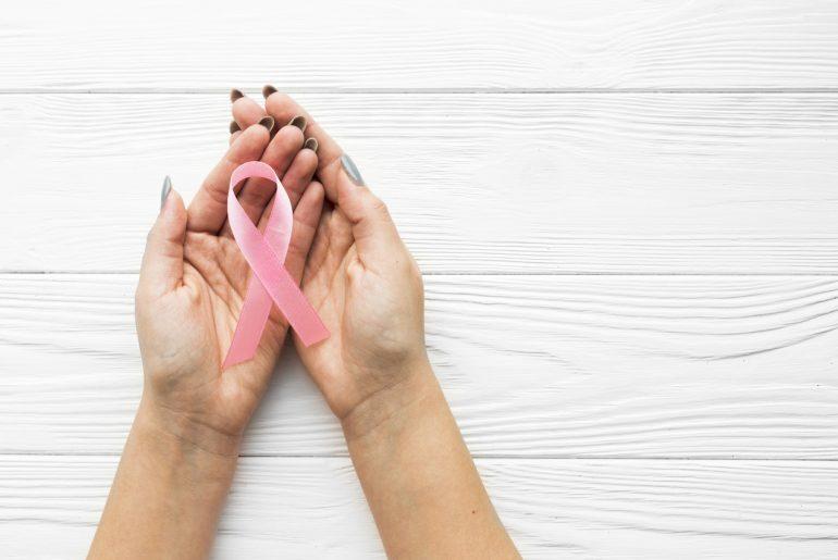 Mulher com laço ícone do Outubro rosa na mão, simbolizando combate ao Câncer de Mama
