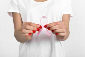 Mulher segurando laço rosa simbolo da luta contra o câncer de mama.