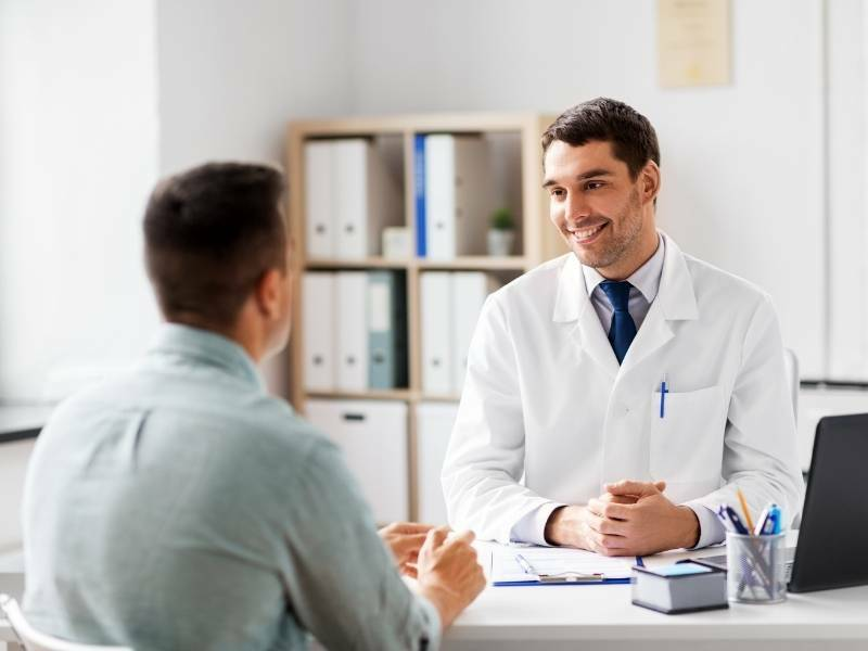 Paciente e médico conversando no consultório urológico.