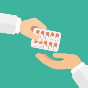 Na imagem, uma mão aparece entregando uma cartela de medicamentos para outra mão.