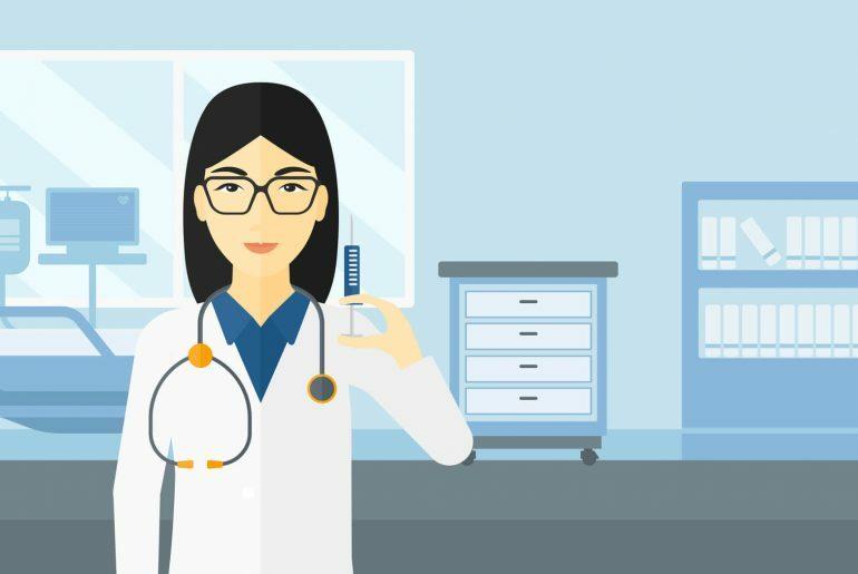 Na imagem, uma médica aparece segurando uma seringa em um ambiente hospitalar.