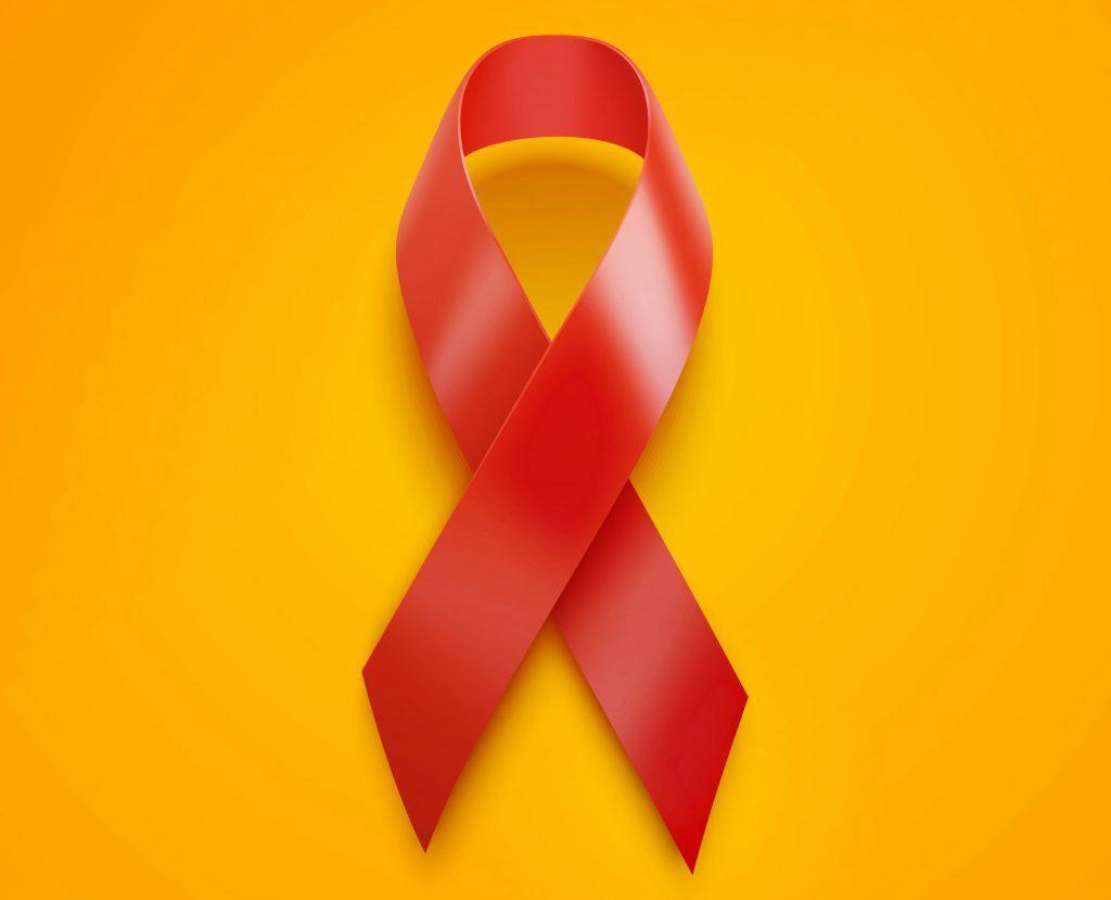 Na foto, um laço vermelho em um fundo laranja.