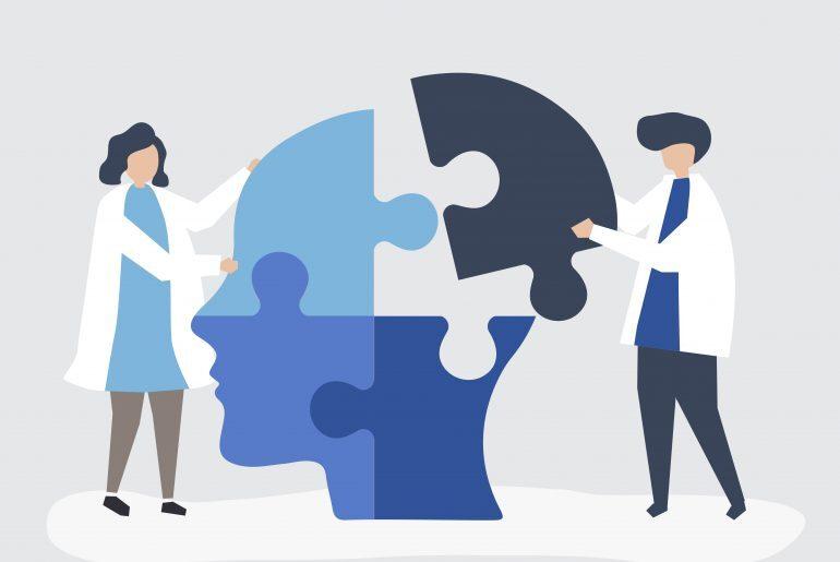 Na imagem, dois profissionais da saúde de jaleco aparecem brincando de encaixar peças de quebra-cabeça de uma cabeça fictícia.