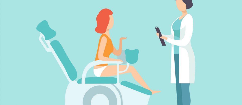 Na imagem, uma paciente sentada em uma cadeira reclinável usada para fazer exames conversa com a médica, em pé.