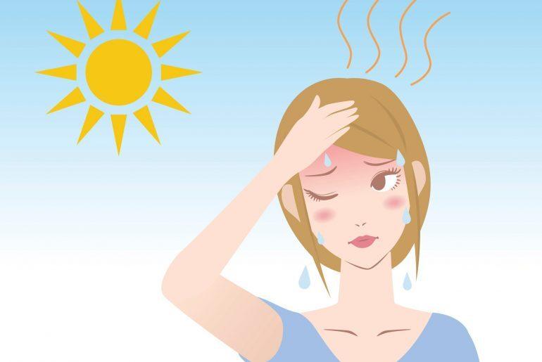 Na imagem, uma mulher com a mão da cabeça e aspecto cansado aparece suando com sol forte ao fundo,