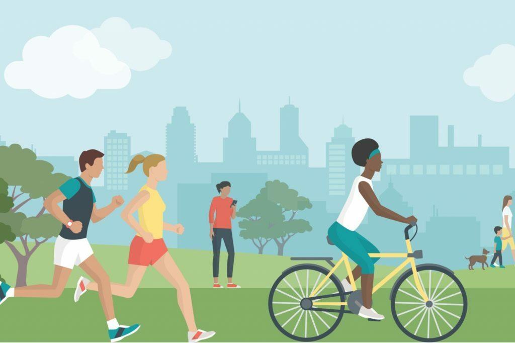 Na imagem mostra pessoas caminhando e andando de bicicleta em um parque durante o dia.