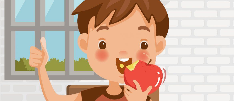 Na imagem, uma criança do sexo masculino aparece comendo uma maçã e fazendo sinal positivo com a mão.