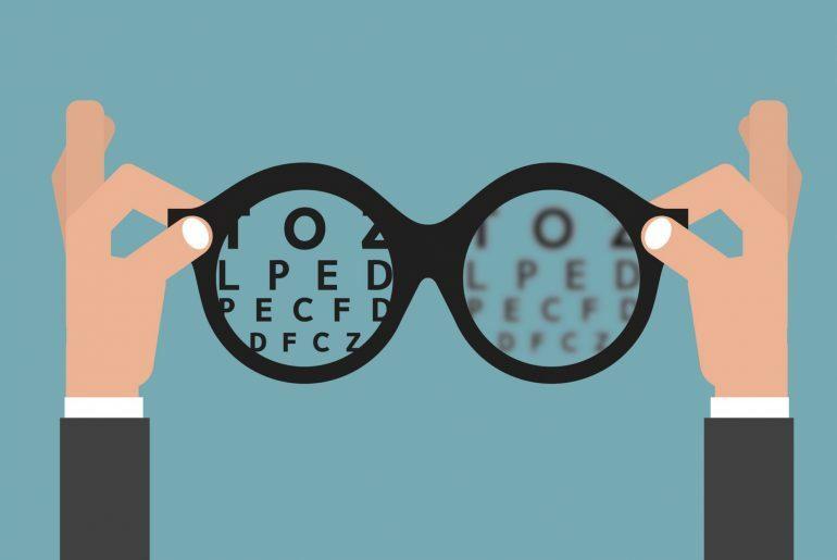Na imagem, um óculos de grau com letras dentro, simulando o exame de refração.