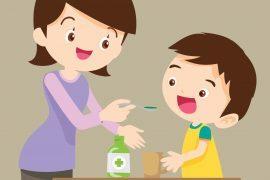 Na imagem, uma mulher - provavelmente mãe - oferece um remédio líquido em uma colher na boca de uma criança.