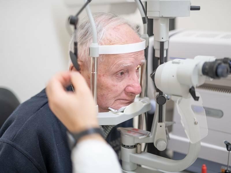 Homem idoso fazendo exames de rotina com oftalmologista.