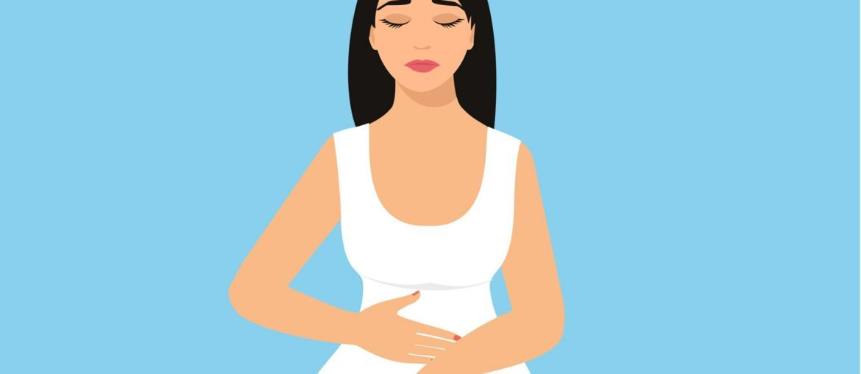 Na imagem, uma mulher vestida de branco com feição incomodada está com a mão na barriga.