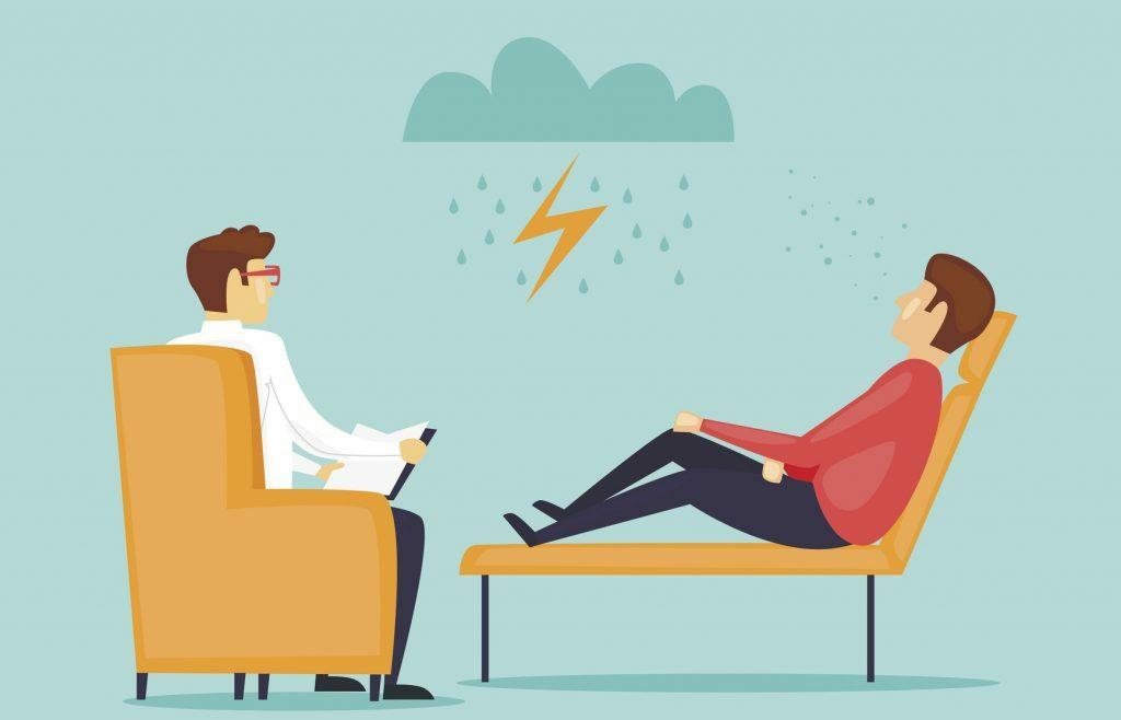 Na imagem, um homem aparece sentado numa cadeira estilo divã, enquanto um psiquiatra a sua frente gesticula.