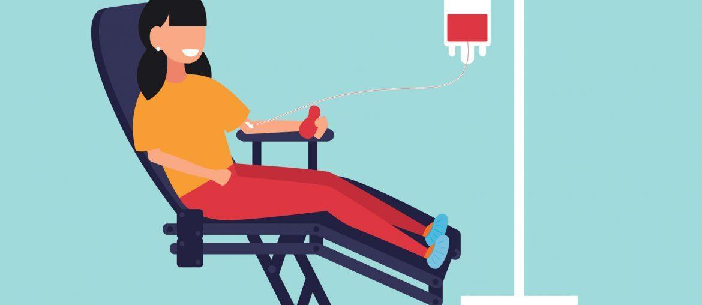 Na imagem, uma mulher aparece sentada numa maca reclinável. Ela está doando sangue.