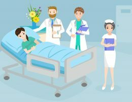Na imagem, uma mulher está deitada em uma maca, enquanto profissionais da saúde estão em volta dela.