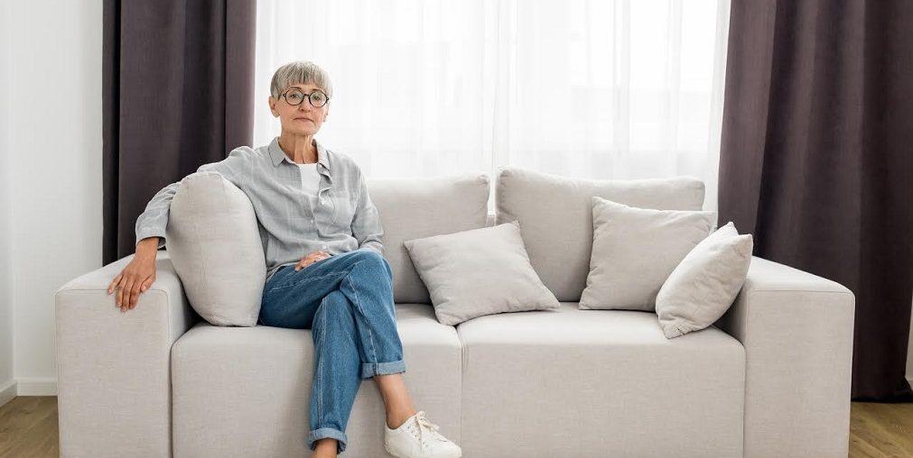 Mulher idosa sentada no sofá.