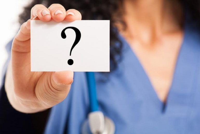 Médico mostrando um papel com interrogação.