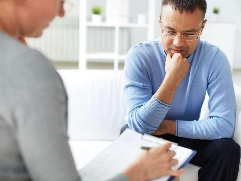 Homem recebendo atendimento de profissional de psicologia.