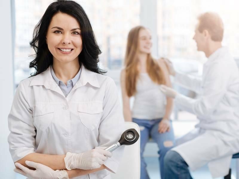 Mulher médica dermatologista com paciente ao fundo.