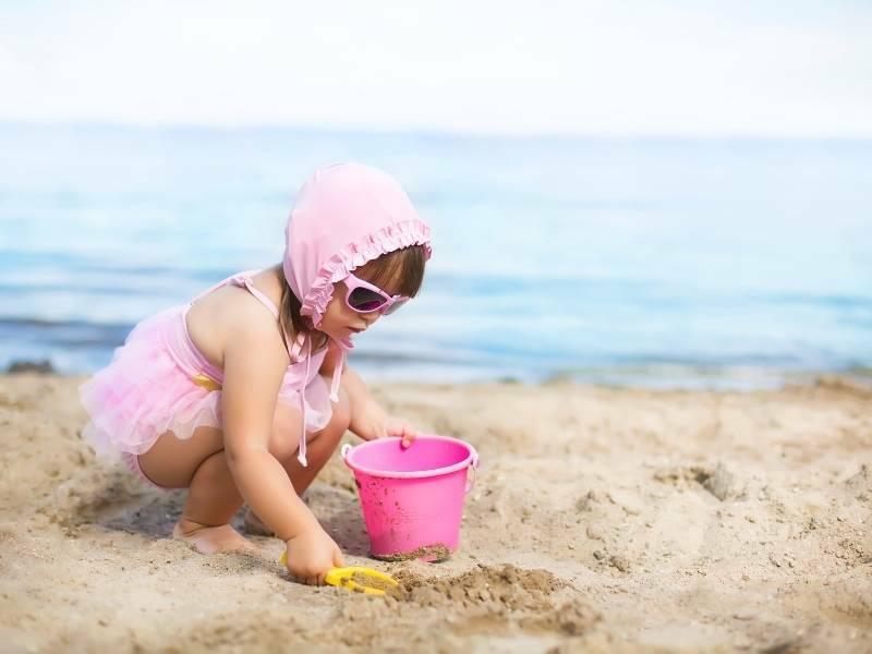 Criança do sexo feminino brincando na areia.