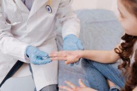 Médico dermatologista examinando a mão de criança.