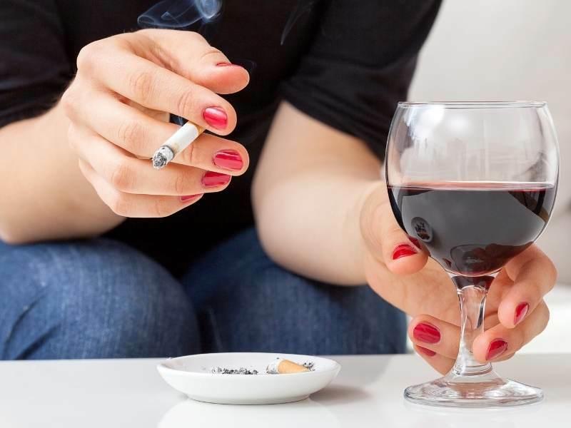 Mulher fumando e bebendo.