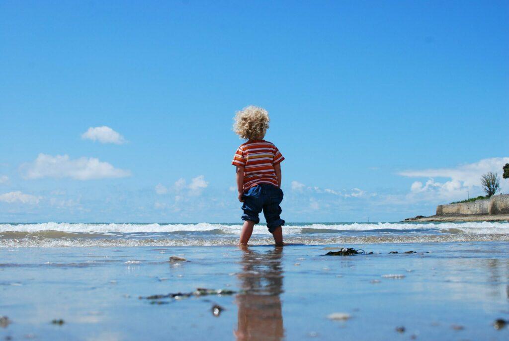 Menino na praia diante das experiências da infância.