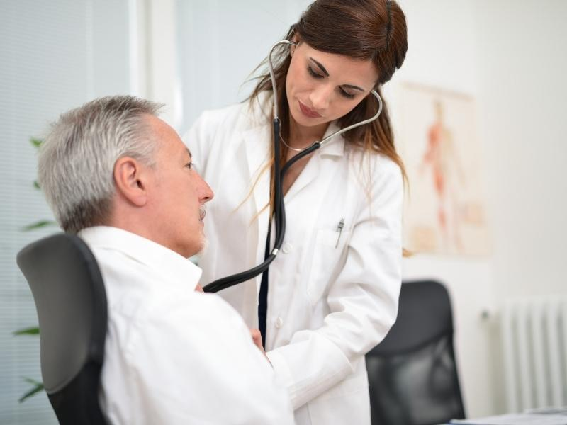 Médica cardiologista fazendo atendimento de paciente homem.