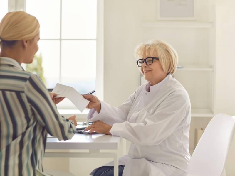 Médica mulher e paciente mulher conversando no consultório.